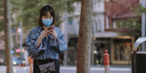 Asian woman walking down the street wearing a protective mask.