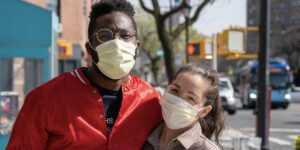 Young couple wearing protective masks outside on a city sidewalk