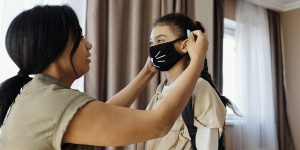 Mother putting on daughter's protective mask with whiskers on it.