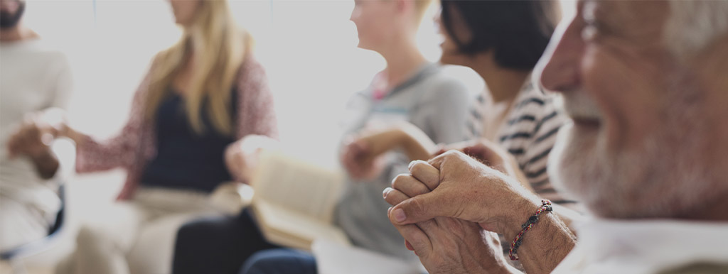 Man holding woman's hand at a support group