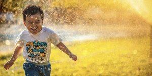 Child running through a sprinkler during summer